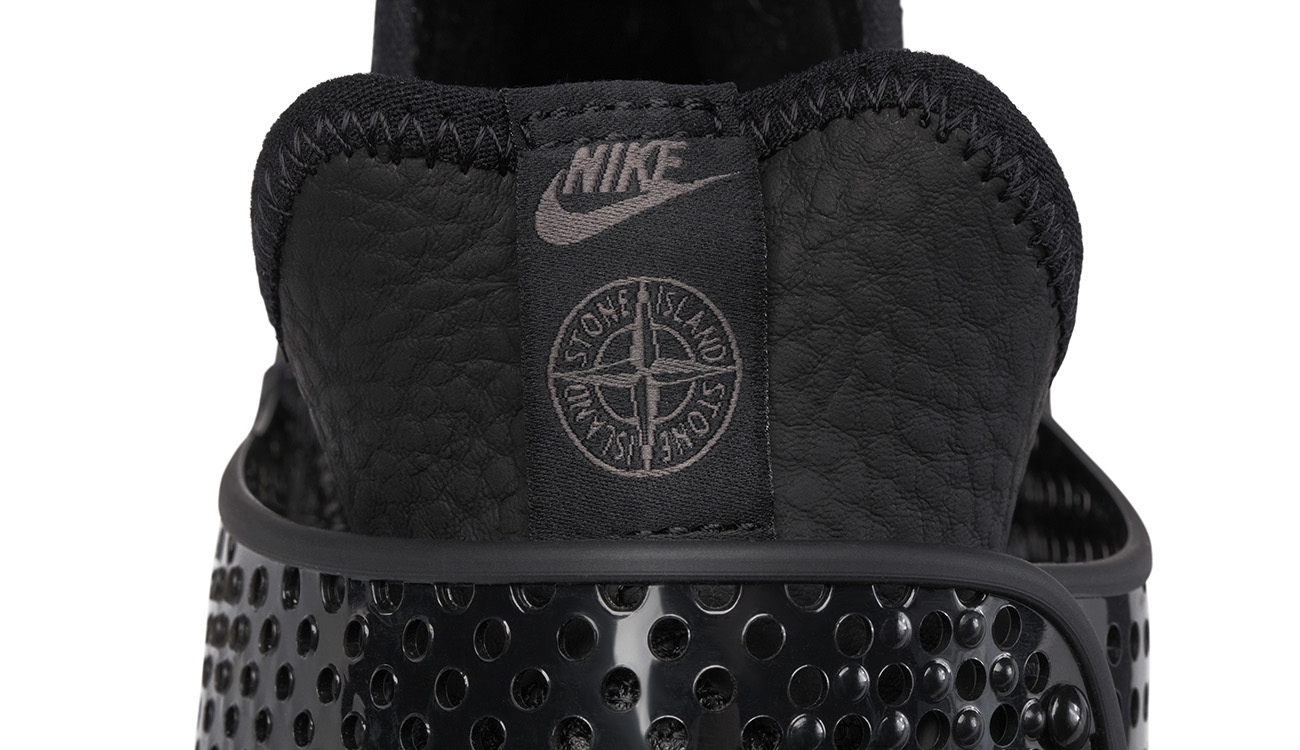 The Nike and Stone Island logos on the back of black, slip on sneaker in synthetic leather.