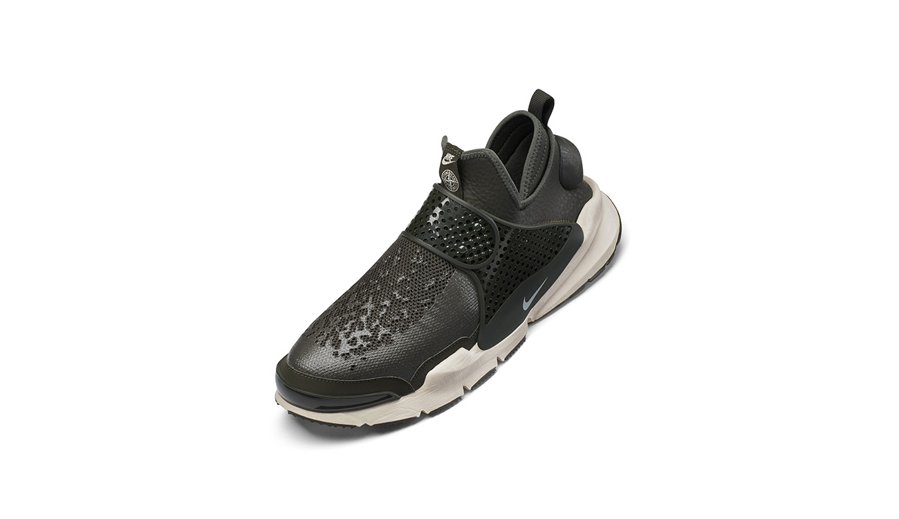 Left foot of black, slip on sneakers, in synthetic leather with mesh upper, midfoot strap and white, chunky outsole.