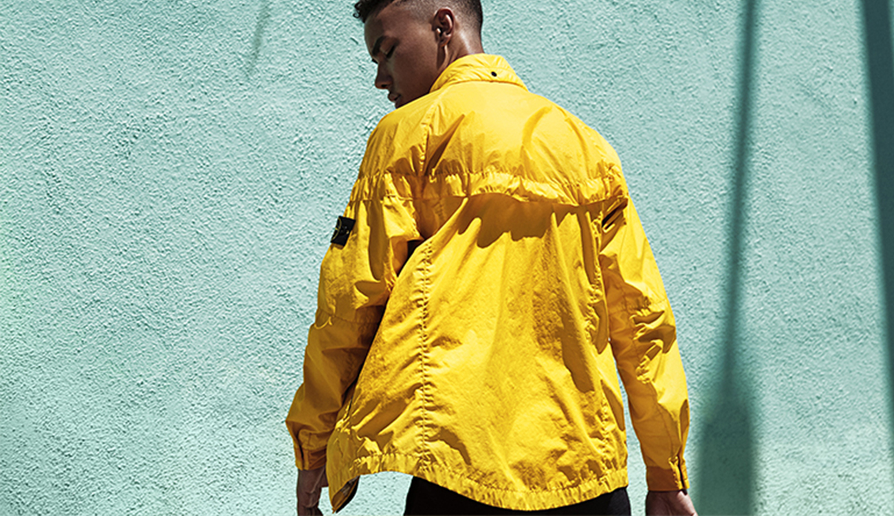 Model wearing a yellow Windrunner jacket showing the back side.