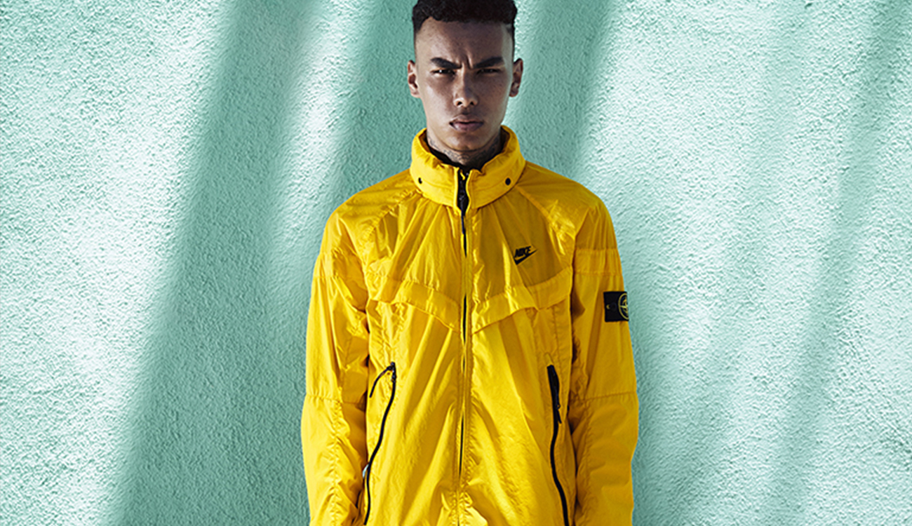 Model wearing a yellow Windrunner jacket with diagonal hand pockets with zip fastening, stand up collar and zip closure.