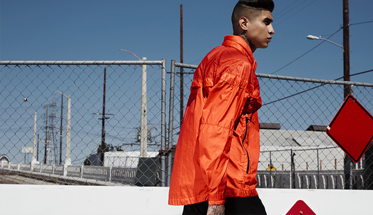 Model wearing a red Windrunner jacket walking in front of industrial landscape.