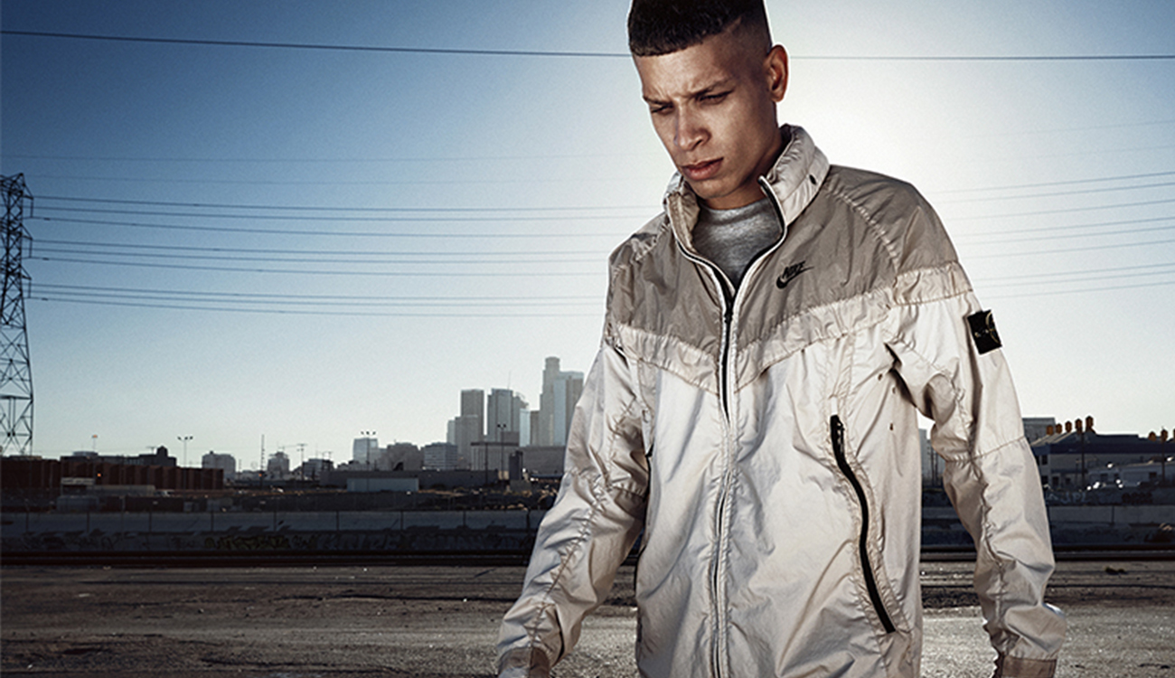 Model wearing a cream Windrunner jacket walking in front of city landscape.