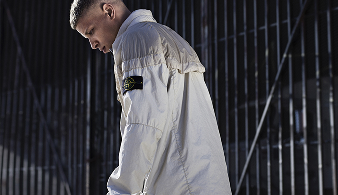 Model wearing a cream Windrunner jacket showing detachable Stone Island badge.