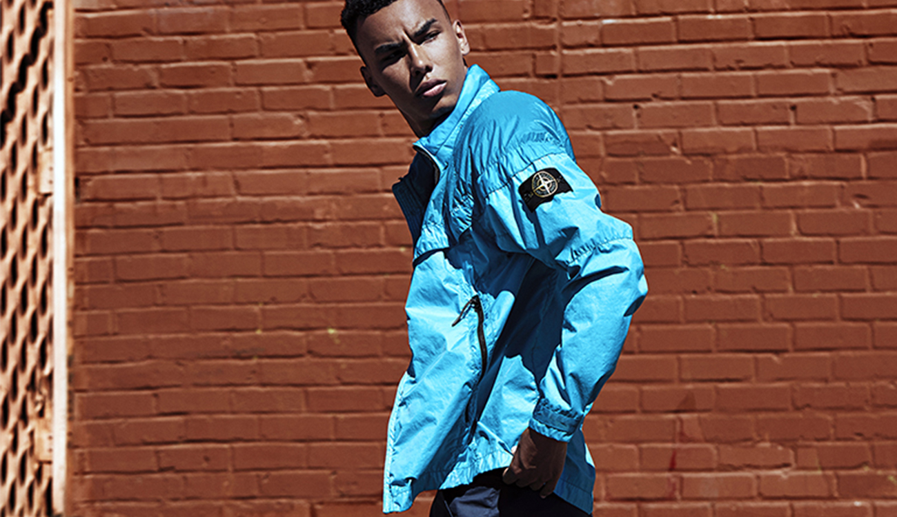 Model wearing a light blue, Windrunner jacket showing detachable Stone Island badge.
