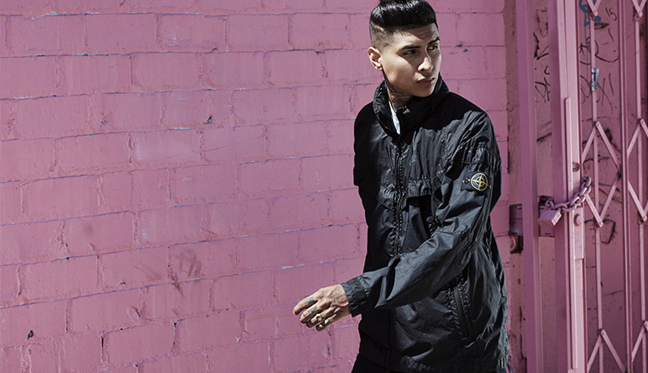 Model wearing a black Windrunner jacket showing detachable Stone Island badge.