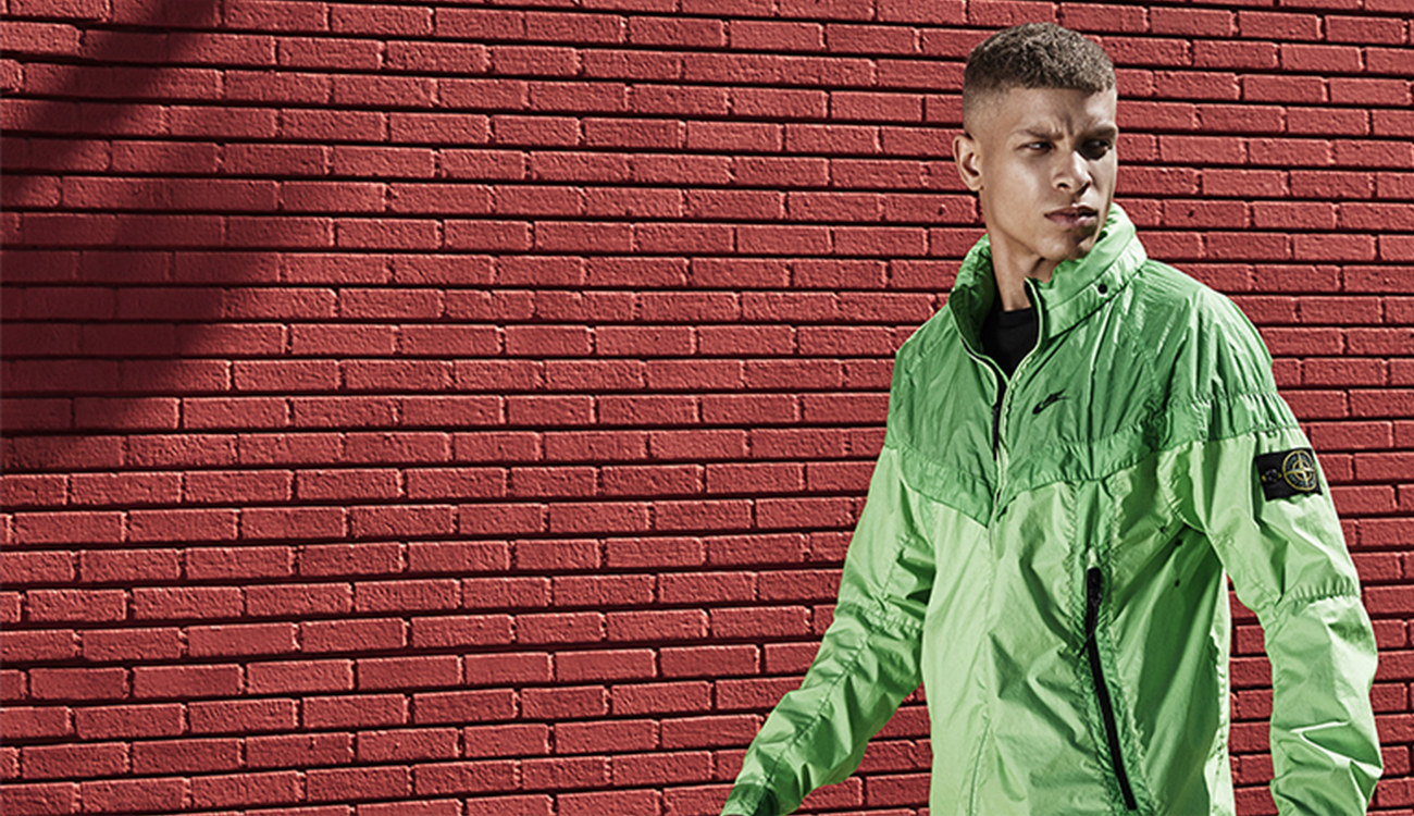 Model wearing a green Windrunner jacket walking beside a red, brick wall.