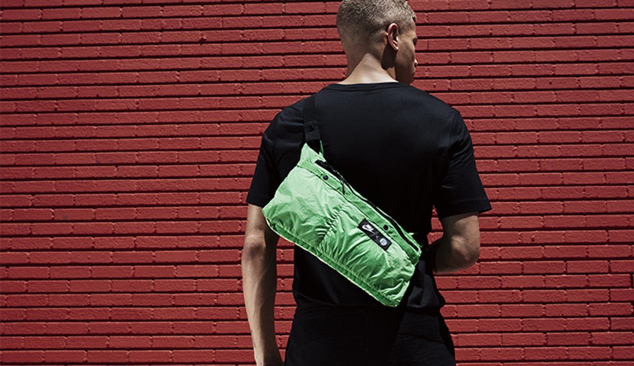 Model wearing a green, lightweight shoulder bag on his back.