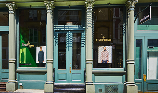 Sunny street view of storefront entrance and two full length windows flanked by four cast-iron columns.
