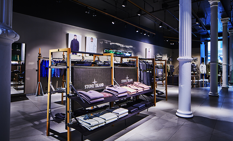 Dimly lit store interior with white structural columns and spotlights on clothes displayed on shelves and racks.
