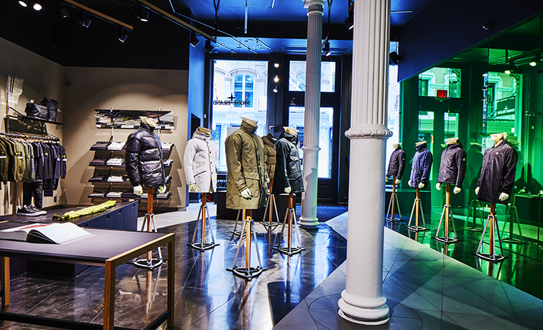 Store interior with mannequins in various different jackets and the Stone Island Archive open on a table.