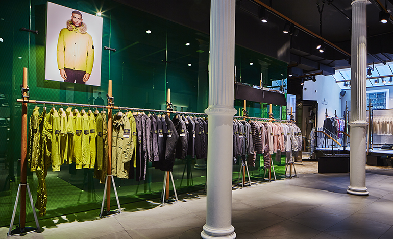 Dimly lit store interior with spotlights on green glass panels and a row of jackets hanging on a clothes rack.