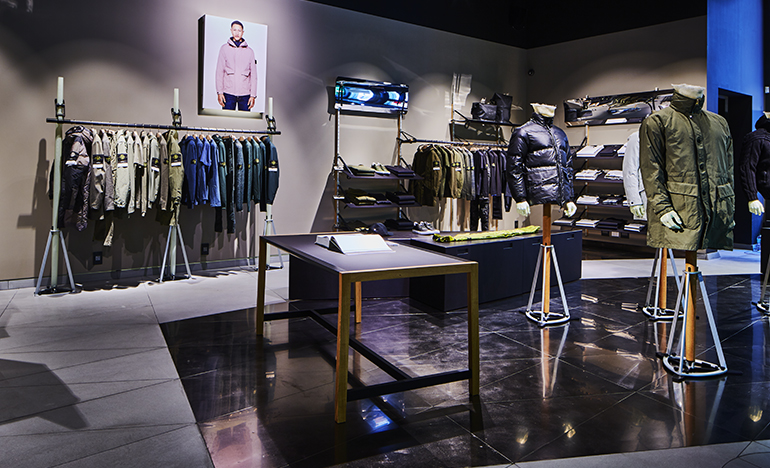 The Stone Island archive open on a table surrounded by merchandise displayed on mannequins and clothes racks.