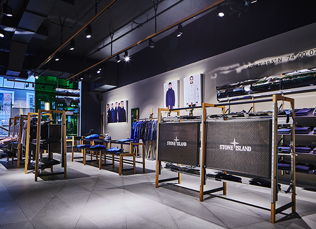 Dimly lit store interior with white, stone floor tiles, black ceiling spotlights and merchandise displayed on contemporary racks and shelves.