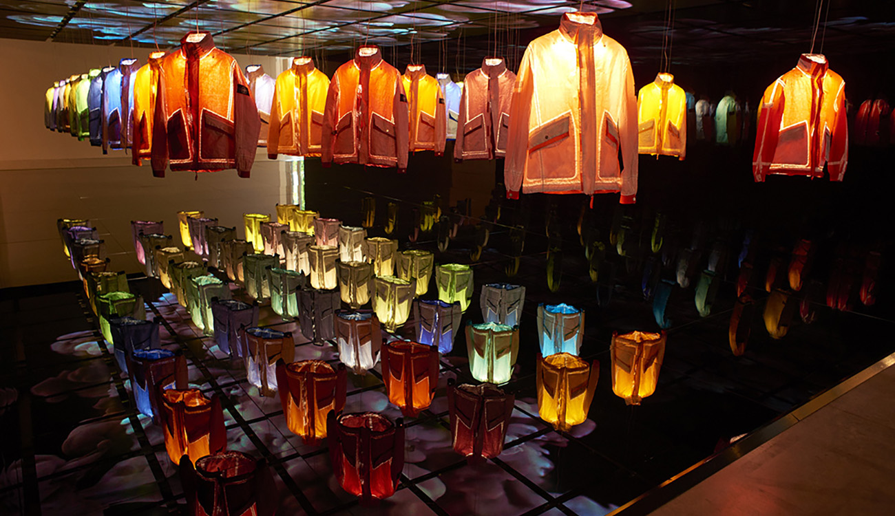 Dark space with 50 jackets in 50 different colors hanging from a mirrored ceiling over a mirrored platform, each one being lit up individually from the inside.