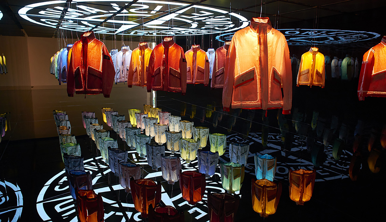 Dark space with 50 jackets in 50 different colors hanging from a mirrored ceiling over a mirrored platform, each one being lit up individually from the inside with the Stone Island compass logo projected onto the ceiling and reflected on the mirrored platform.