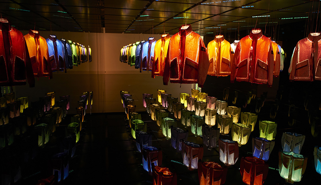 Dark space with 50 jackets in 50 different colors hanging from a mirrored ceiling over a mirrored platform, each one being lit up individually from the inside with words projected onto the ceiling and reflected on the mirrored platform.