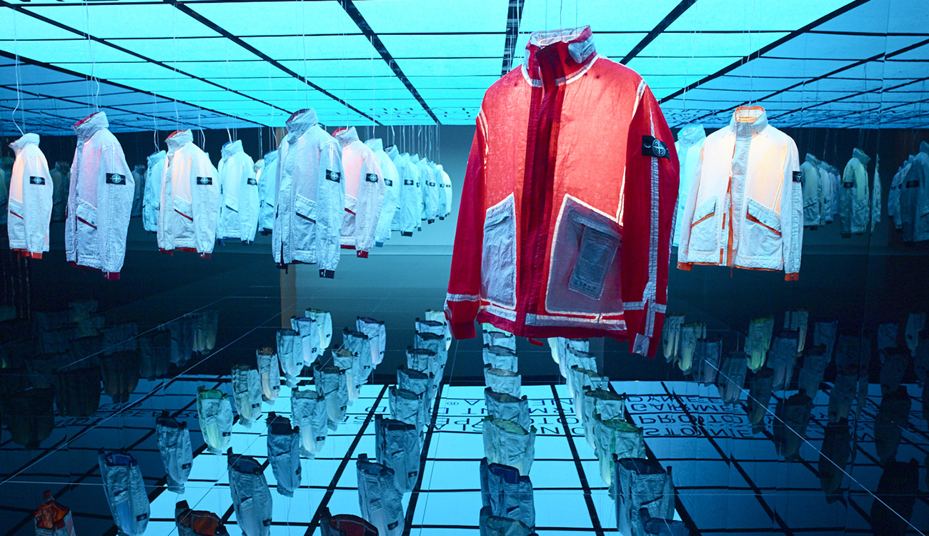 Artistic installation of reversible, lightweight jackets in Dyneema flexible composite fabric all showing the white side except for one showing a red side.