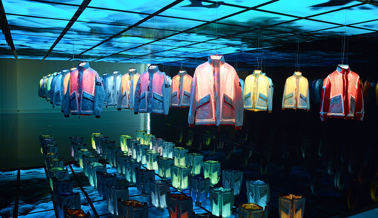 Artistic installation of jackets hanging from the ceiling and lit up individually from the inside to show their individual colors.