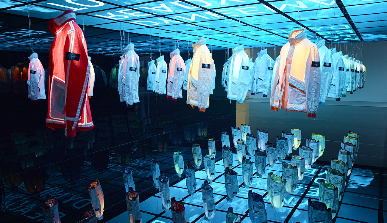 Side view of artistic installation of jackets hanging from the ceiling and lit up individually from the inside to show their individual colors.