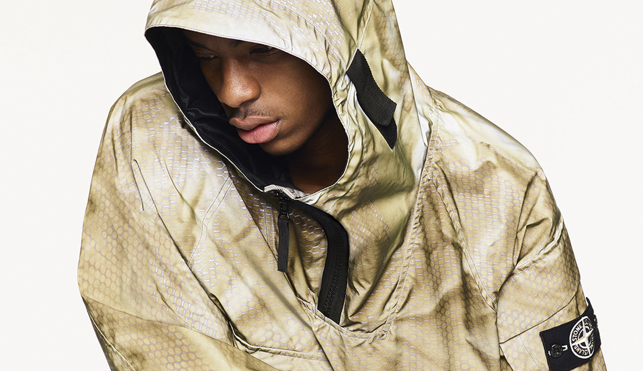 Model wearing two tone gold anorak in highly reflective fabric with hood and zip closure.