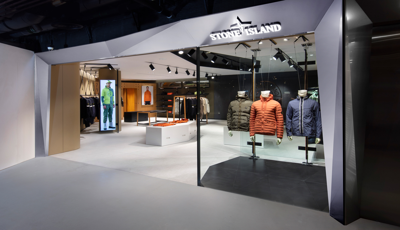View into store showroom from the entrance, with three jackets displayed on mannequins in the window and large photos of models on two walls