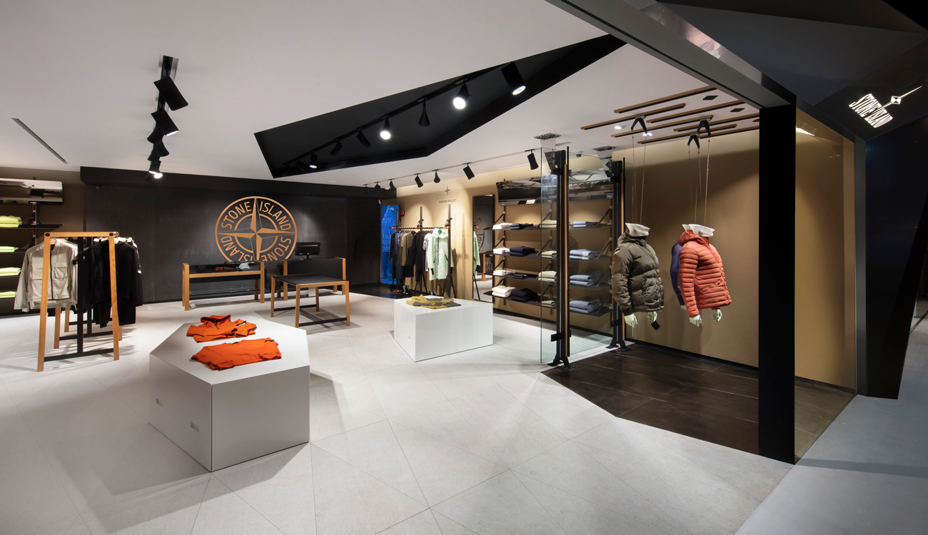 Interior view of store showroom from outside, at an angle, with clothing displayed on stands, racks, and shelves, and large Stone Island logo on the black back wall