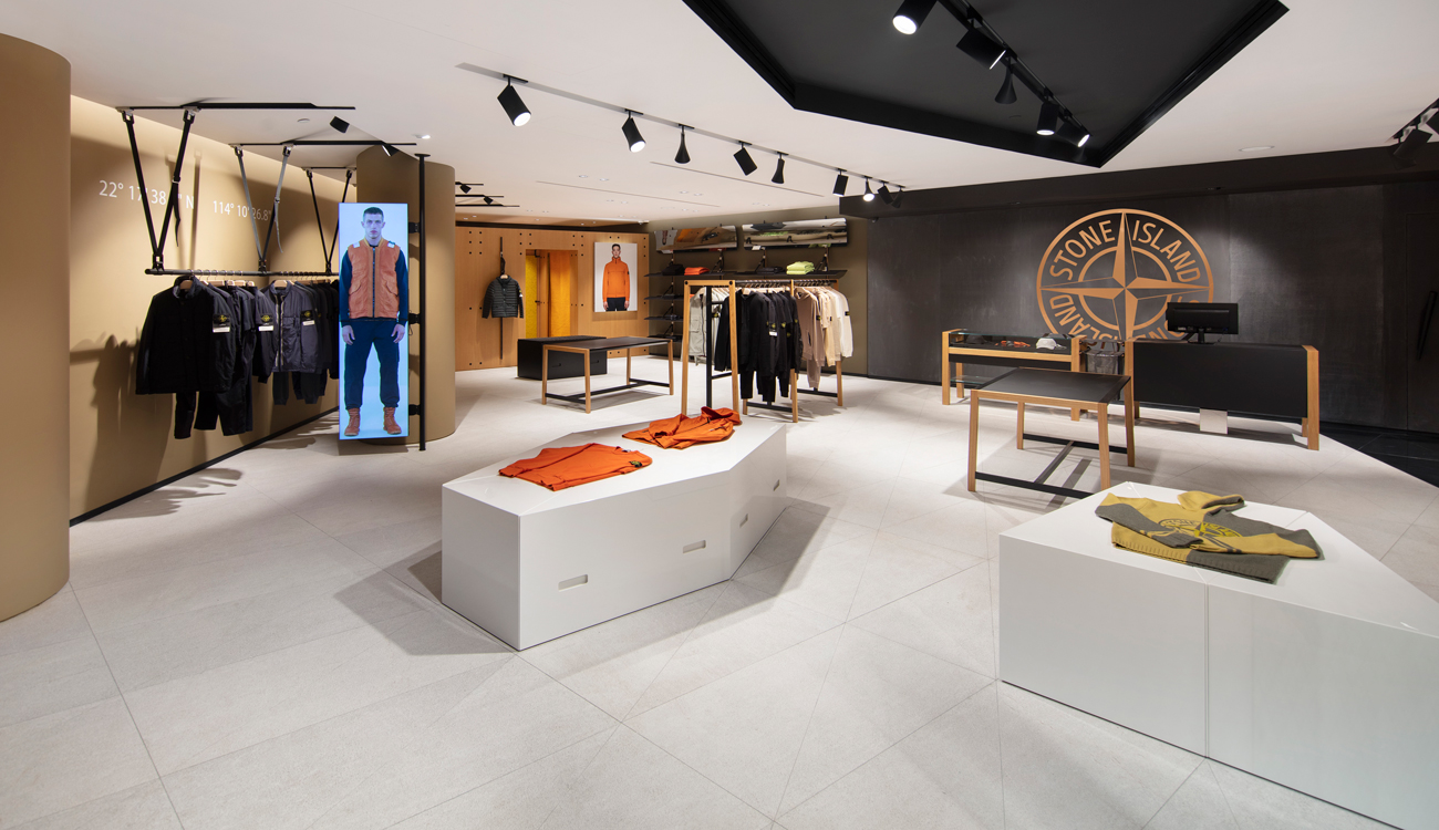 Interior view of store showroom with clothing displayed on stands, racks, and shelves, two large photos of models in orange jackets on the side walls, and large Stone Island logo on the black back wall