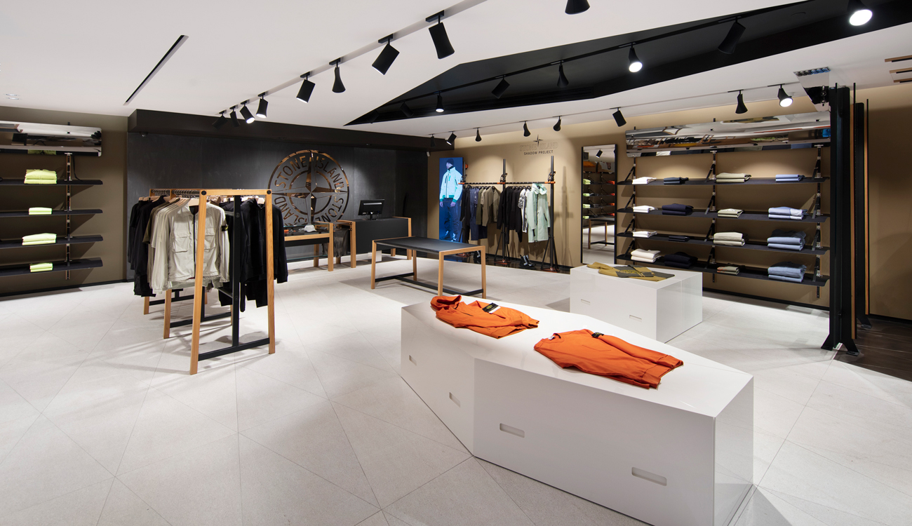 Interior view of store showroom with clothing displayed on stands, racks, and shelves, and large Stone Island logo on the black back wall