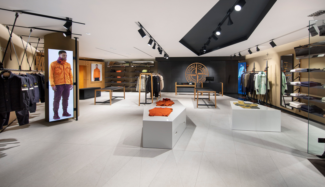 Store interior with clothing displayed on stands, shelves, and racks, and large photos of models in orange jackets shown on two walls