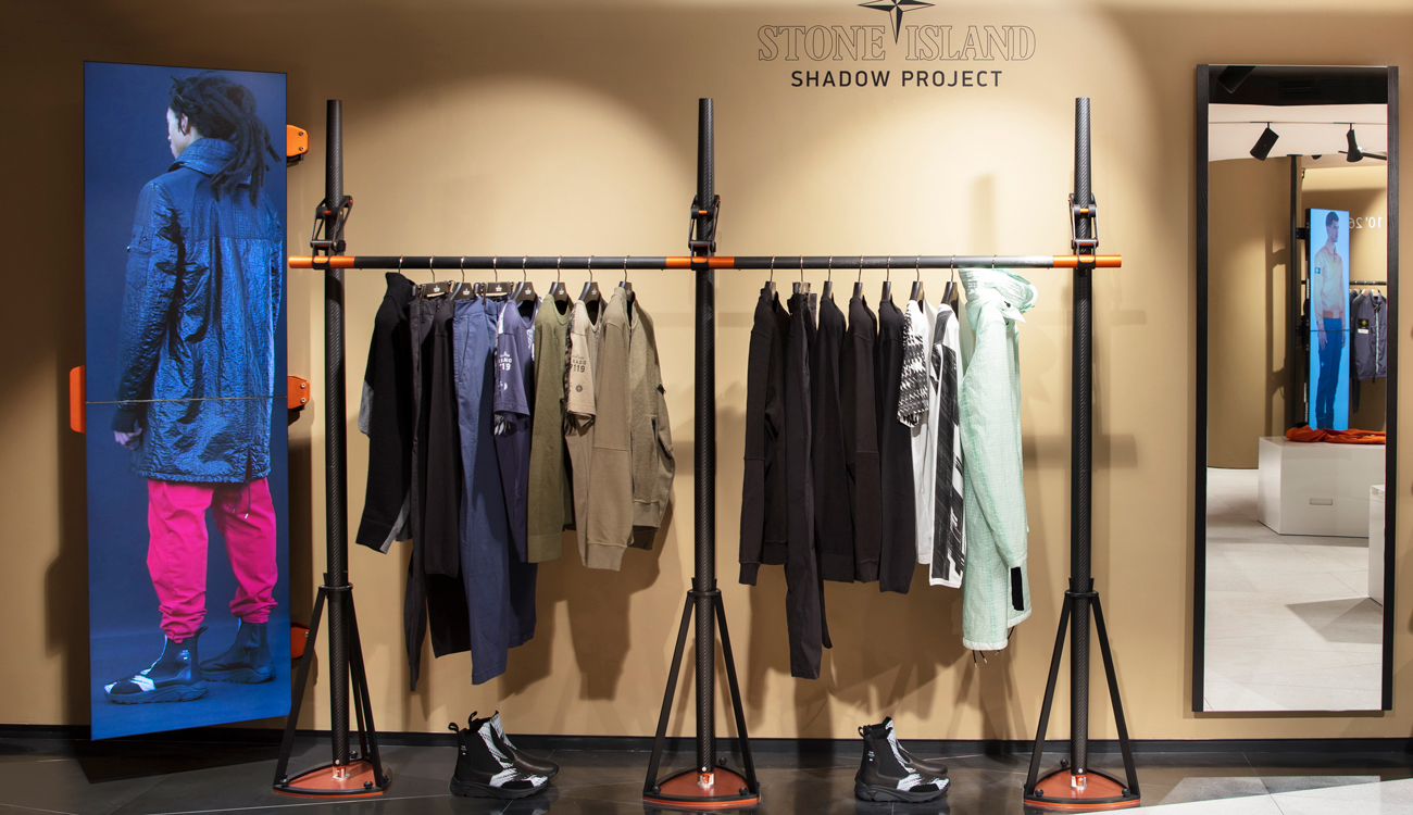 In store Shadow Project display, with garments hanging on a rack above shoes and next to a large photo of a model with his back to the camera, wearing a technical coat and red pants