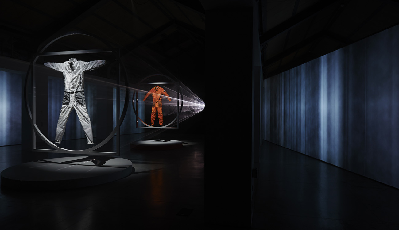 Artistic installation of a white jumpsuit and an orange one. Each one is framed in a square within a circle. The orange one is behind the white and they are lit from behind by lasers emanating from the Stone Island compass logo.