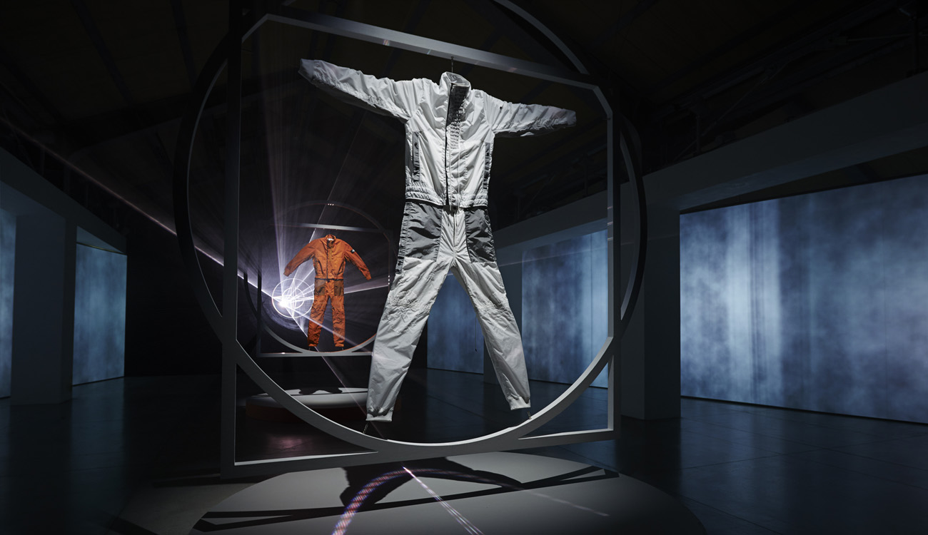 View from below of artistic installation of a white jumpsuit and an orange one. Each one is framed in a square within a circle. The orange one is behind the white and they are lit from behind by lasers emanating from the Stone Island compass logo.