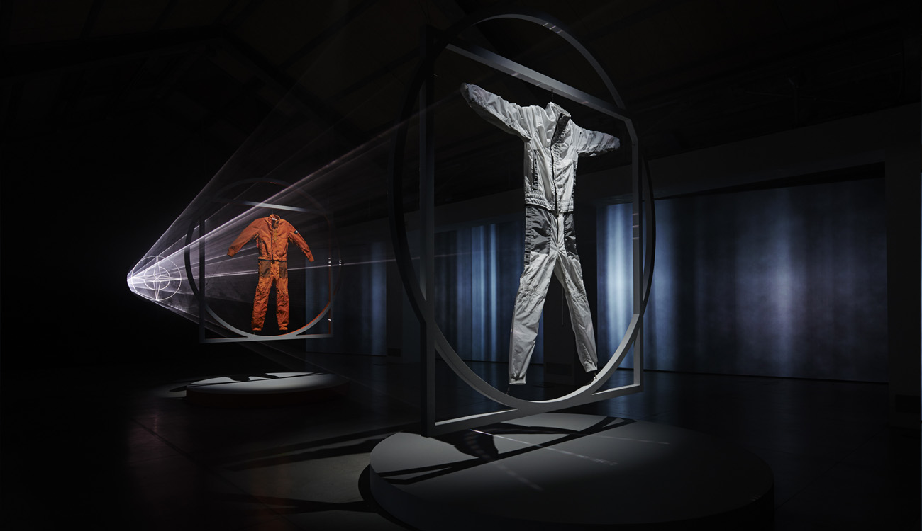 View from left angle of artistic installation of a white jumpsuit and an orange one. Each one is framed in a square within a circle. The orange one is behind the white and they are lit from behind by lasers emanating from the Stone Island compass logo.