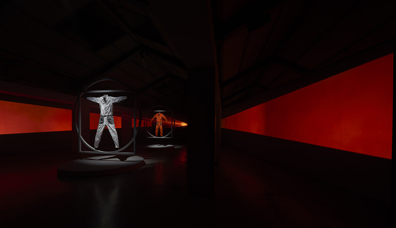 Jumpsuit installation framed within two diagonal rows of red lit panels and lit from behind with red laser beams.