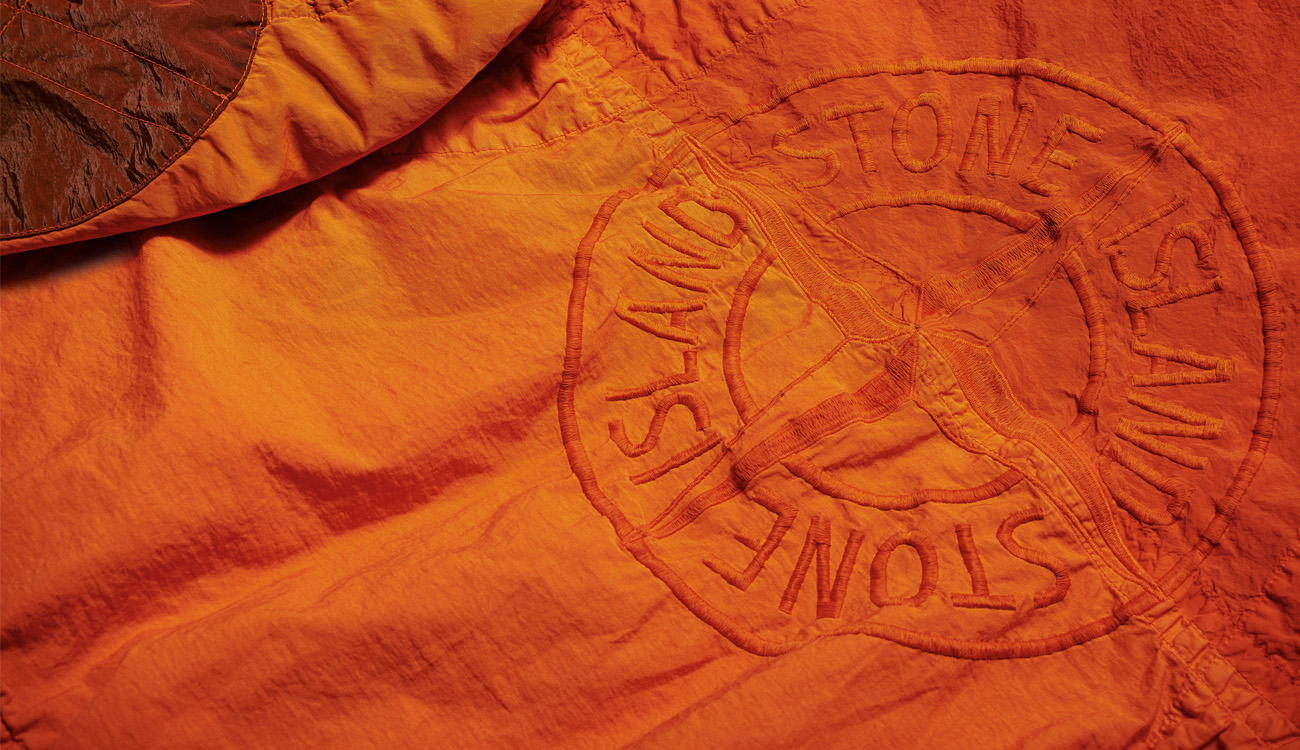 The Stone Island compass logo embroidered in orange on orange jumpsuit top part.