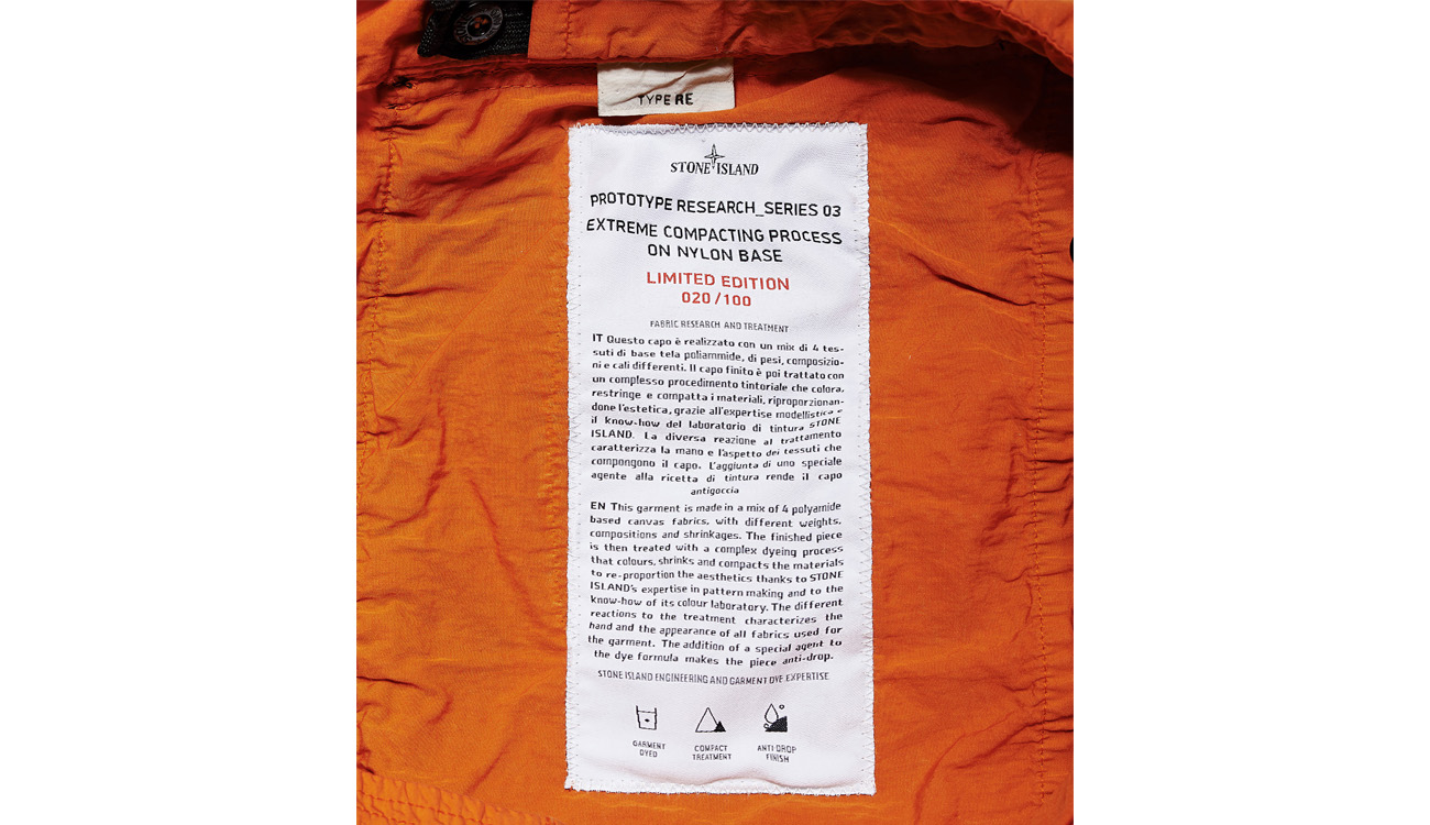 Clothes' label on orange jumpsuit giving information about the garment's fabric.