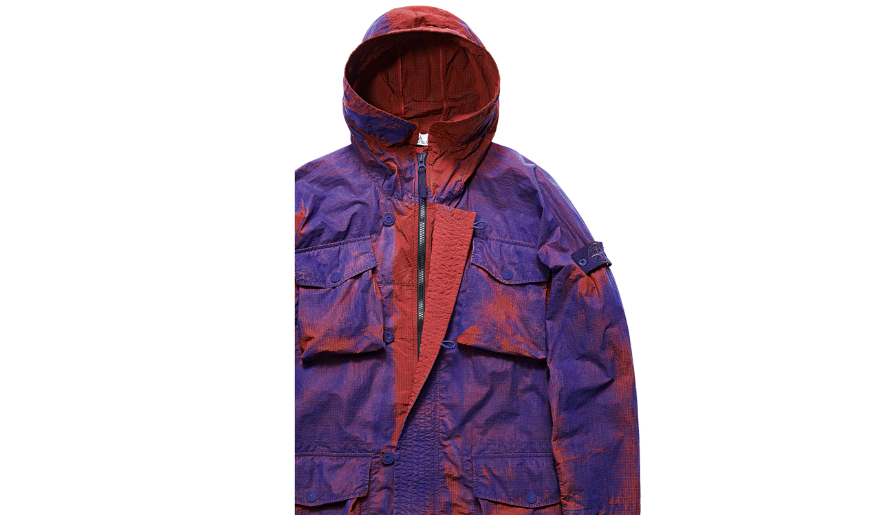 Jacket with hood up and concealed zipper closure revealed.