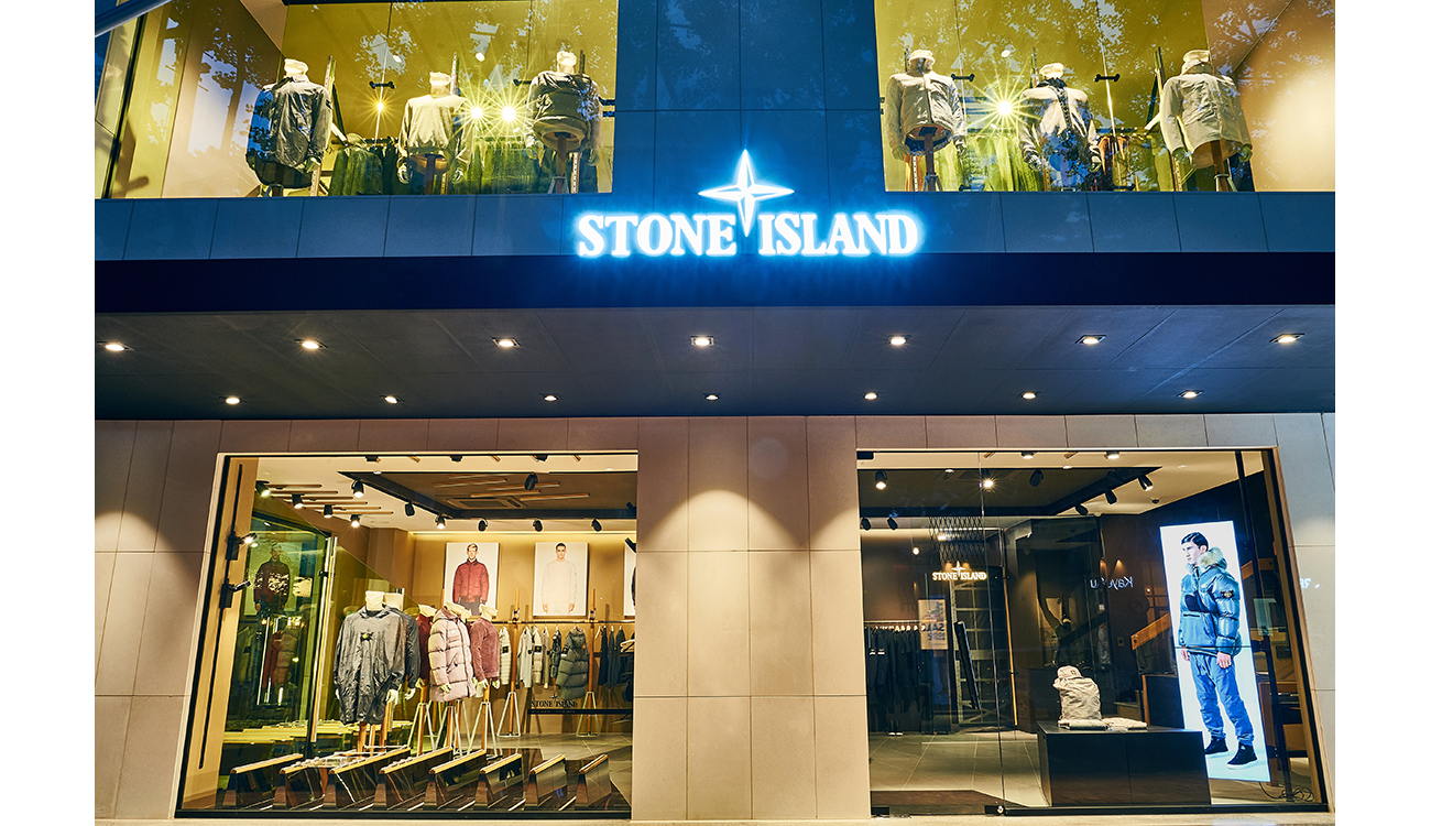 Storefront with the Stone Island logo in neon lights centered between four, full length windows and a glass door showing two floors.