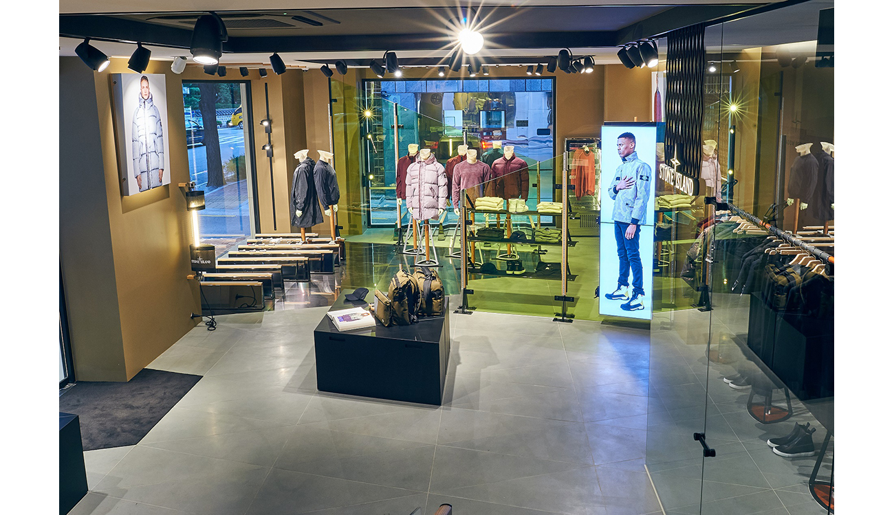 Archetypal, Stone Island store interior featuring black, ceiling spotlights, white stone floor tiles and industrial style store fittings.