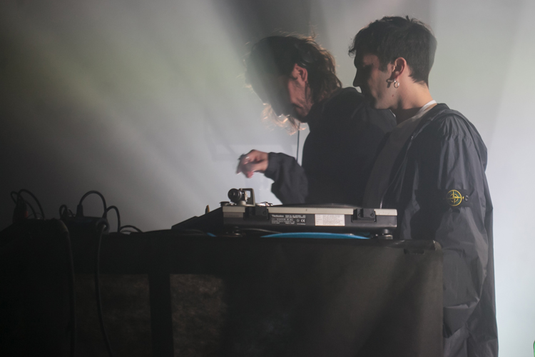 Two men in profile at DJ equipment on stage, one in a black jacket with Stone island badge on upper arm