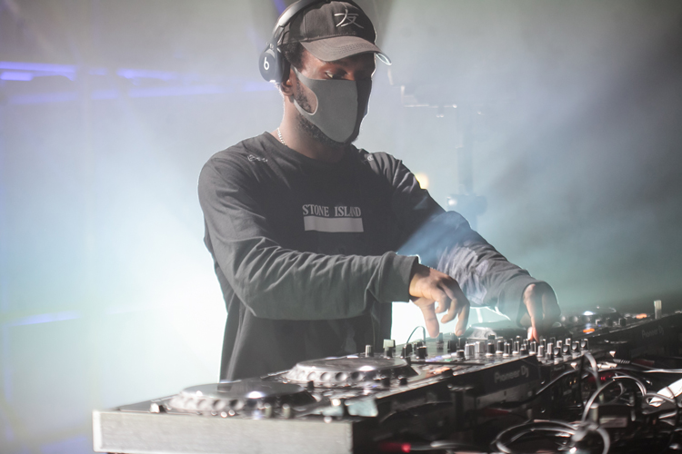 Man wearing baseball cap, headphones, black mask, and Stone Island logo T-shirt handling DJ equipment on stage