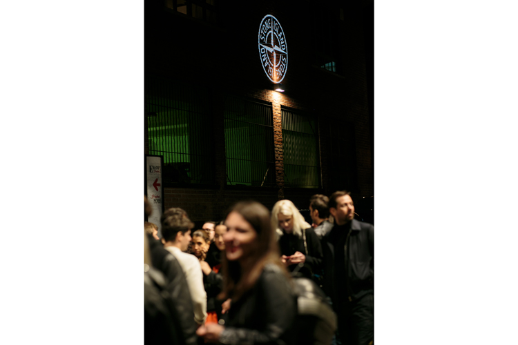 Crowd standing outside a brick building with Stone Island logo projected on the wall