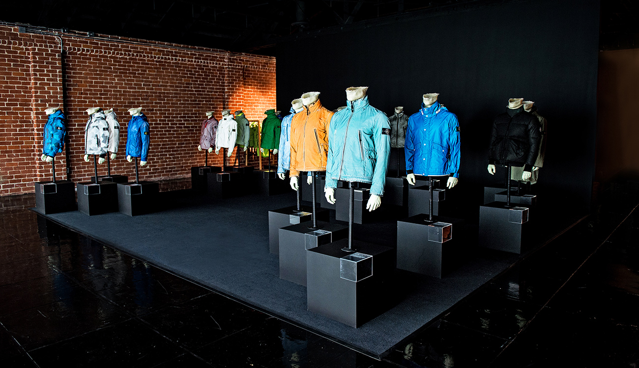 Installation of mannequins on plinths wearing jackets in different colors and styles.