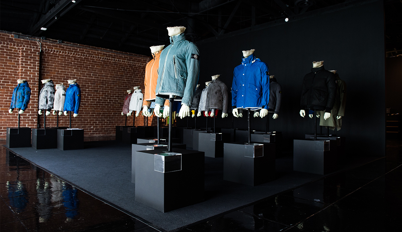 Side view of installation of mannequins on plinths wearing jackets in different colors and styles.