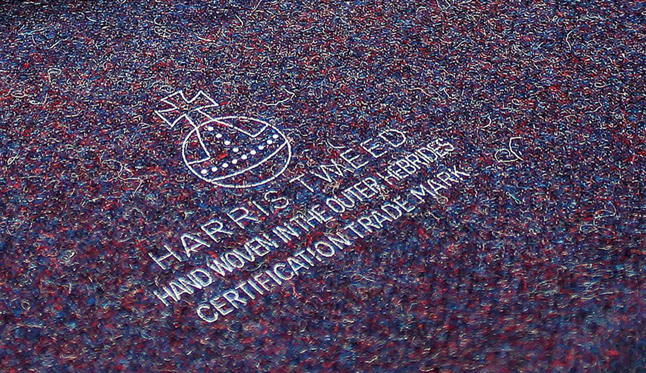 Close up of white printed graphic on Harris Tweed fabric, with the words Harris Tweed, Hand Woven in the Outer Hebrides, Certification Trade Mark.