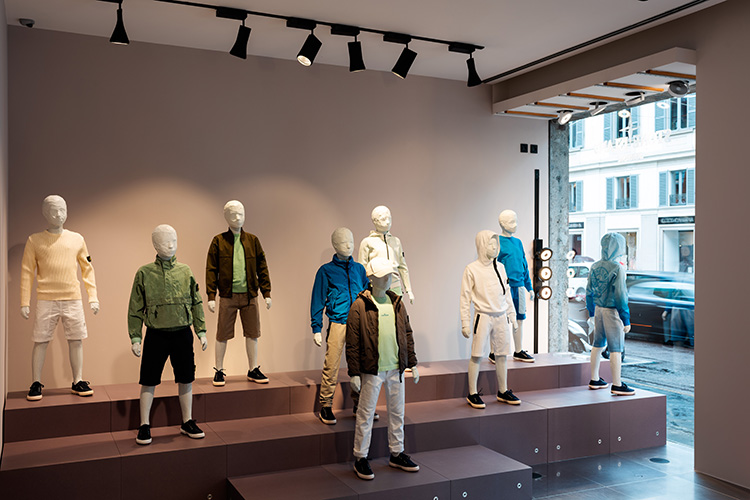 Nine junior mannequins wearing Stone Island Junior clothing in different styles and colors including white, blue and green.