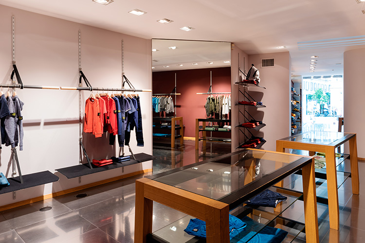 Store interior showing mirrored wall and merchandised displayed on contemporary racks, shelves and tables.