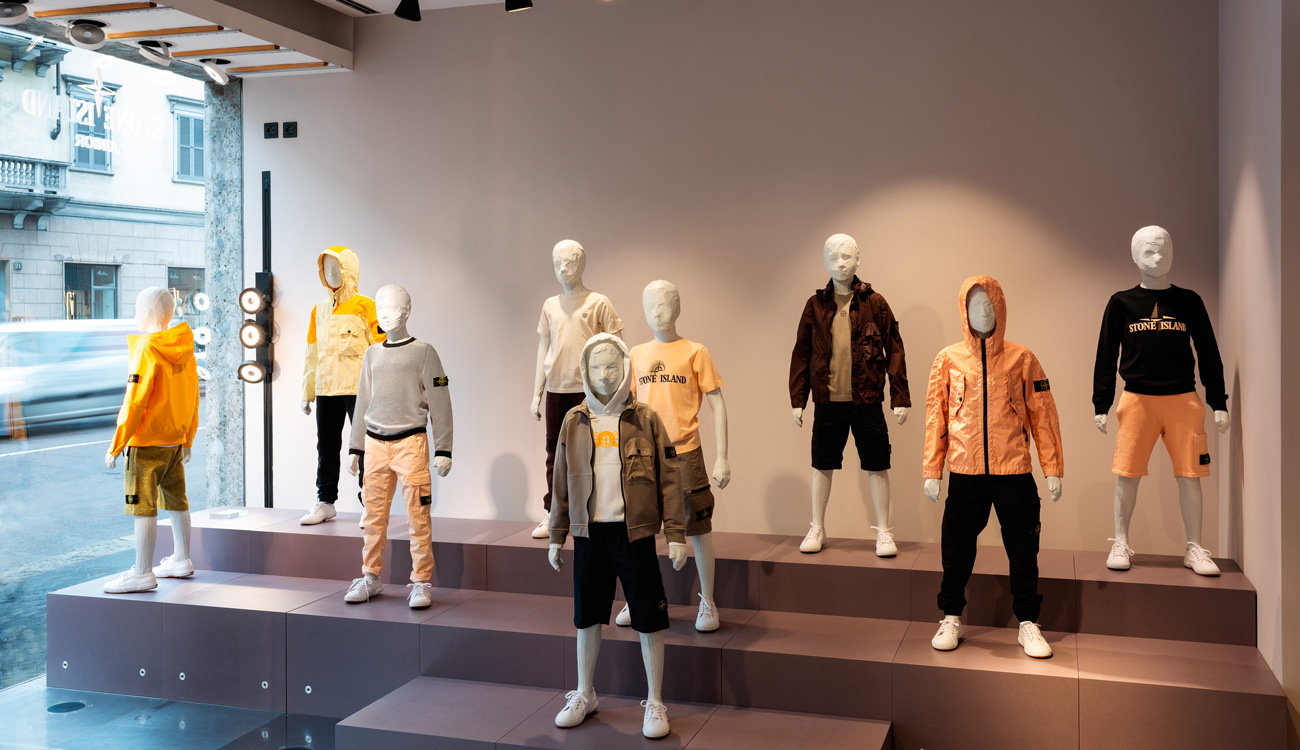 Nine junior mannequins wearing Stone Island Junior clothing in different styles and colors including black, yellow and orange.