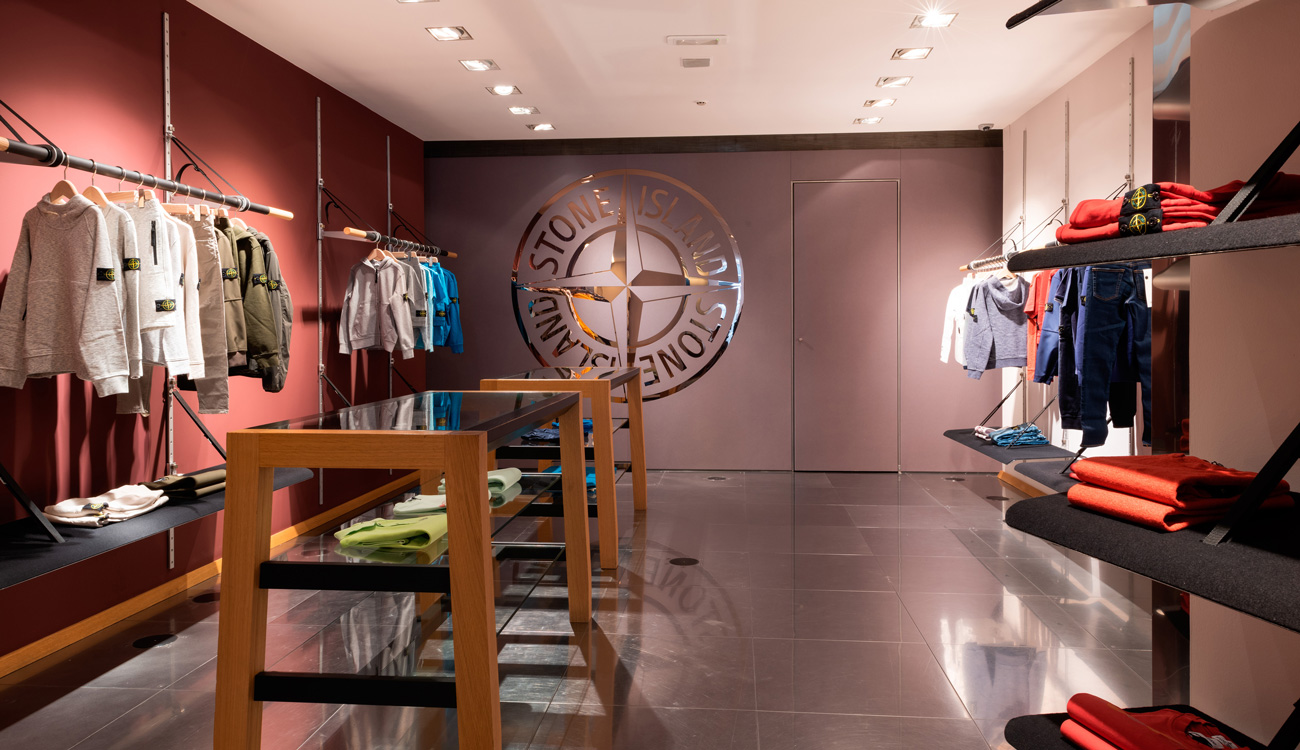 Store interior showing white ceiling, dark colored floor tiles and merchandise displayed on contemporary store fittings.