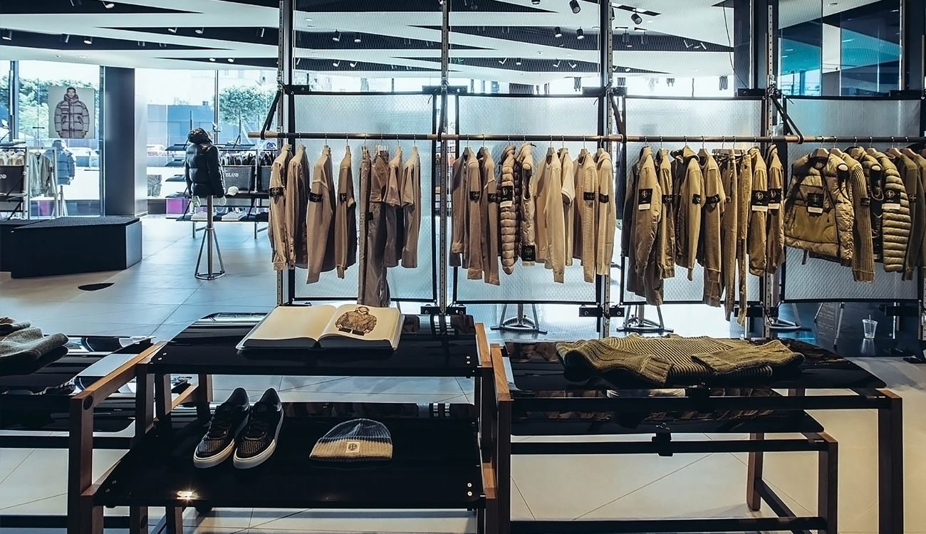 Brightly lit, contemporary store interior with a row of beige colored jackets and tops hanging on a clothes rack and the Archive open on a table.